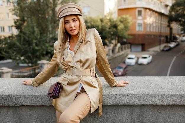 Buitenbeeld van elegante europese vrouw die in de herfststad loopt. beige pet en jasje. stijlvolle accessoires.
