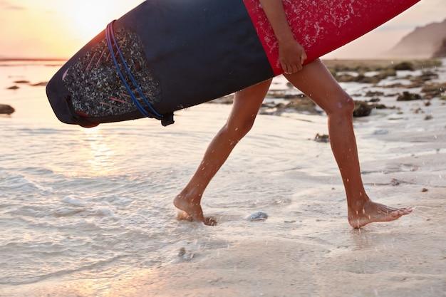 Buitenbeeld van vrouwelijke surfer die in beweging wordt gefotografeerd