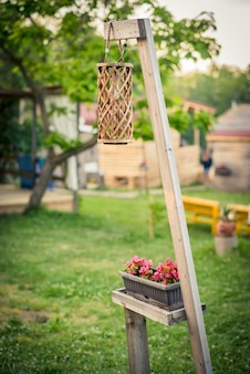 Buitendecoratie - een rieten tuinlantaarn en een bloempot op een houten voet.