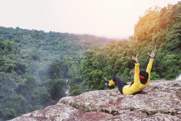 Buitenexcursies op klif met uitzicht op de bergen / buitenavontuur en reizigersvrouw ontspannen op natuurbostoerist tijdens vakantiereizen avontuurlijke backpacktochten reizen