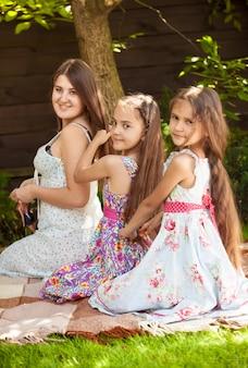 Buitenfoto van drie lachende zussen die kapsels doen