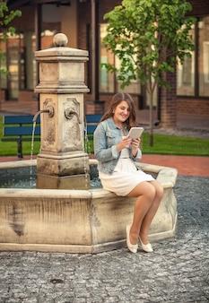 Buitenfoto van een mooie vrouw die een boek leest op tablet aan de zijkant van de fontein