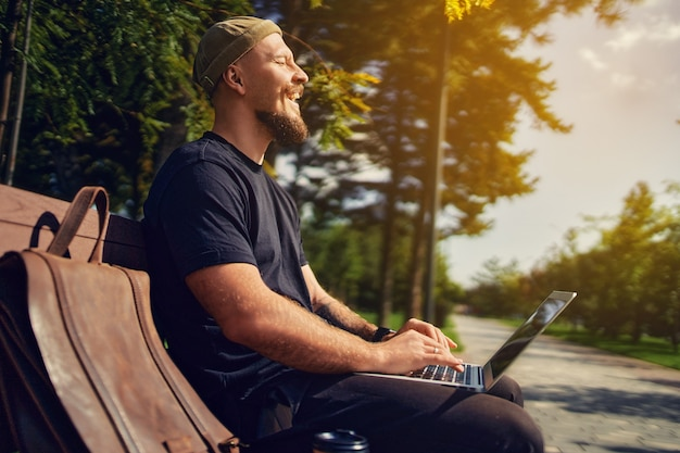 Buitenfoto van lachende millennial met bril zit op een bankje terwijl hij op een laptop werkt