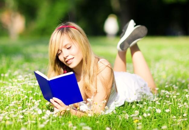 Buitenfoto van lief tienermeisje met boek