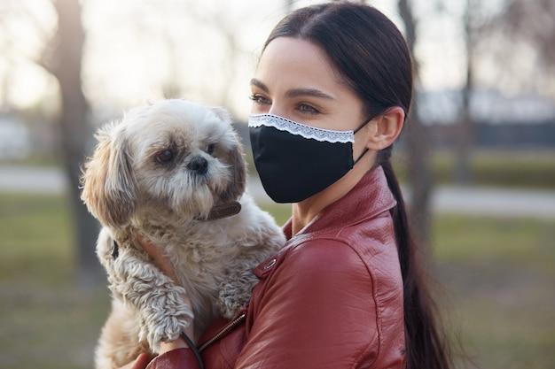Buitenfoto van opgetogen mooie jonge vrouw die antibacterieel masker draagt ter bescherming tegen coronavirus, witte maltese hond in handen houdt, loopt, dierenvriend is