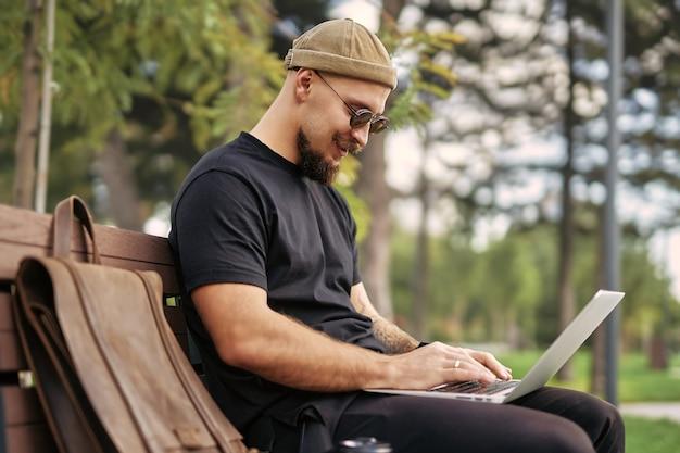 Buitenfoto van positieve millennial in zonnebril die op een bankje zit en op laptop in stadspark werkt