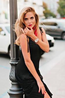 Buitenfoto van prachtige geïntrigeerde dame in zwarte jurk die naast ijzeren pilaar staat