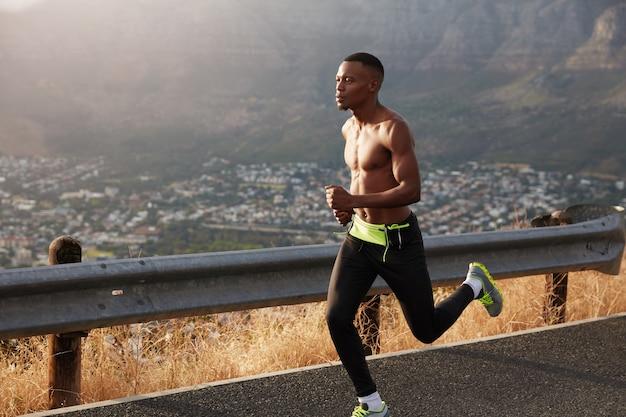 Buitenfoto van sportman rent op landelijke bergweg, gefotografeerd in beweging, heeft atletische lichaamsvorm, traint joggen bij warm weer, traint uithoudingsvermogen, probeert niet te stoppen voor pauze