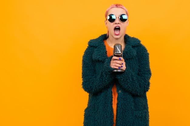 Buitengewoon mooie vrouw met kort roze haar in donkere jas en zonnebril zingt in een microfoon geïsoleerd op een oranje achtergrond