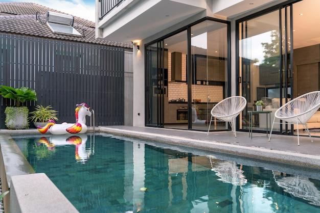 Buitenhuis met zwembad en drijvende eenhoorn in het huis