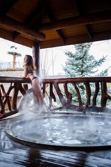 Buitenjacuzzi. jacuzzi met een meisje. mooie figuur vrouw in een zwembroek. meisje in het zwembad met warm water op het terras, lichaamsbehandelingen in de spa. ontspan in de open lucht, wellness. huisje met bubbelbad