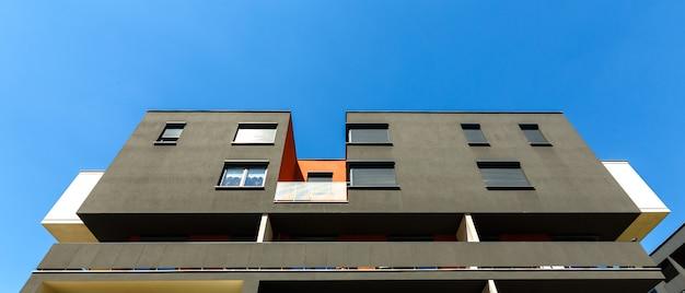 Buitenkant van een modern zwart flatgebouw op een blauwe hemel