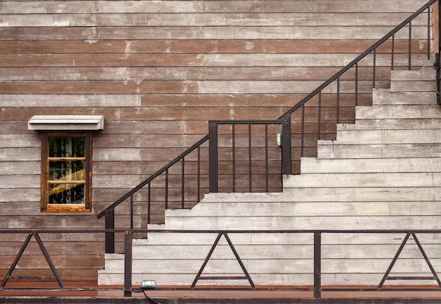 Buitenkant van hardhouten gebouw met raam en trap