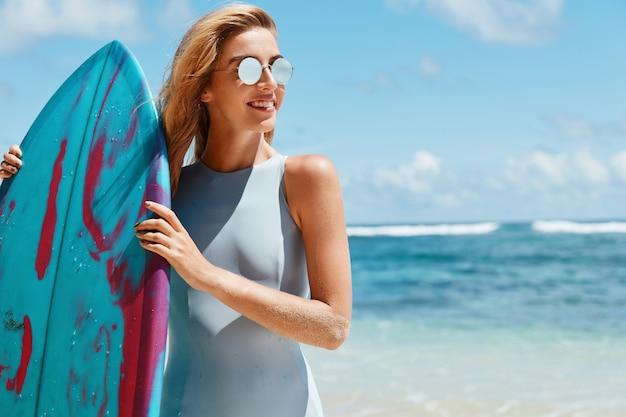 Buitenopname van actieve vrouwelijke surfer in tinten, draagt blauw badpak, houdt surfplank vooraan, gaat watersportwedstrijden houden, staat terug naar de oceaan met kopie ruimte voor uw reclame