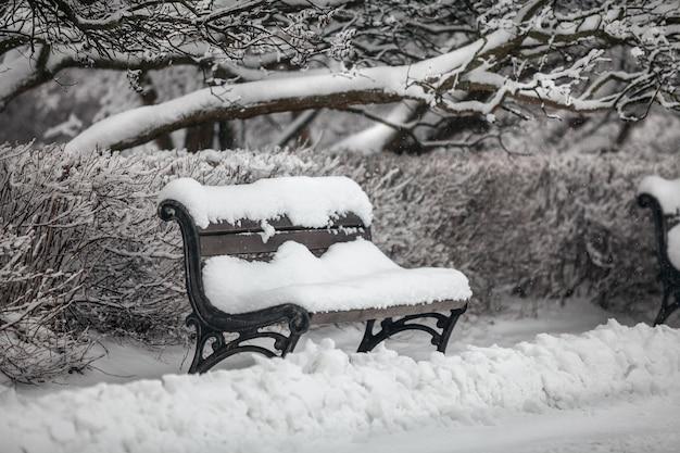 Buitenopname van bank in park bedekt met sneeuw