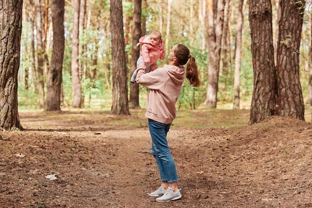 Buitenopname van een liefhebbende vrouw die haar dochtertje in de lucht overgeeft