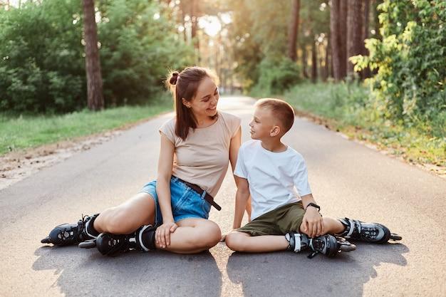 Buitenopname van een mooie vrouw die met haar zoon op de asfaltweg zit, casual kleding en rolschaatsen draagt, familie die rust rolschaatst, elkaar aankijkt en praat.
