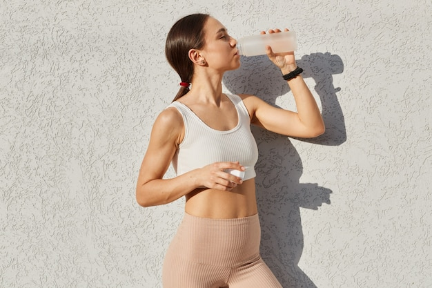 Buitenopname van een mooie vrouwelijke hardloper die buiten staat in de buurt van een grijze muur die drinkwater uit een fles drinkt