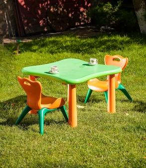 Buitenopname van plastic kinderstoel en tafel op gras op het erf