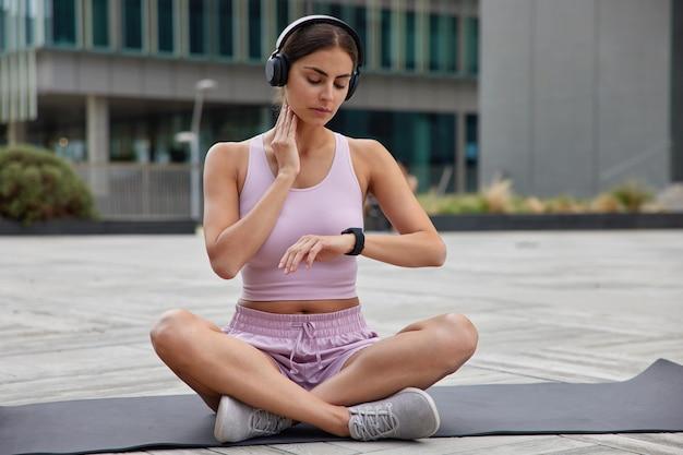 Buitenopname van sportvrouw controleert pols na training houdt hand op nek kijkt naar polshorloge zit gekruiste benen op karemat gekleed in activewear-treinen in open lucht