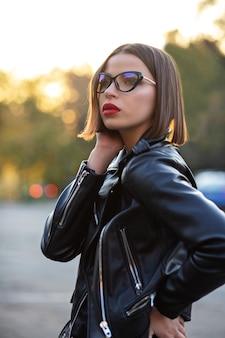 Buitenportret van een elegant gebruind model met een zwarte jas en een bril die op straat poseert