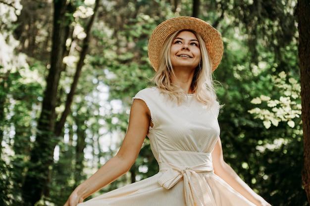 Buitenportret van een jonge vrouw met een strohoed die de zoom van haar witte jurk vasthoudt tijdens een wandeling in het park of bos