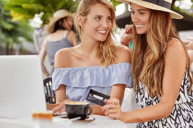 Buitenportret van stijlvolle vrouwelijke lesbiennes bladert op internet op moderne draagbare laptopcomputer, maakt online winkelen en betalen, verheugt zich op nieuwe aankopen, geniet van aromatische drank in café met terras
