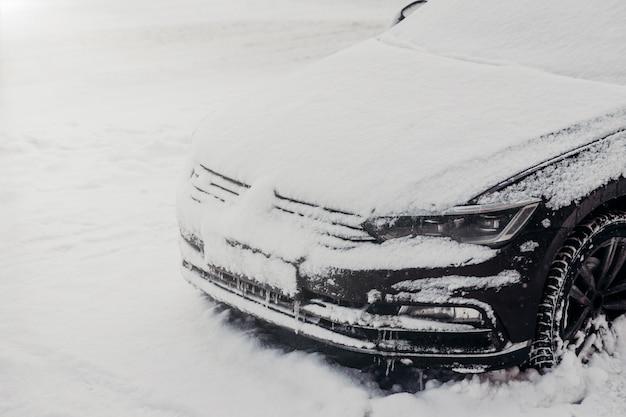 Buitenschot van auto bedekt met witte sneeuw, vast in sneeuw tijdens sneeuwval in de winter