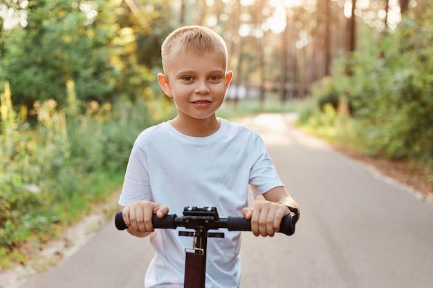 Buitenschot van een gelukkig blond jongetje dat met zijn scooter speelt op de asfaltweg in het zomerpark, een schattig kind met een wit casual t-shirt, een gelukkige jeugd, een gezonde levensstijl.