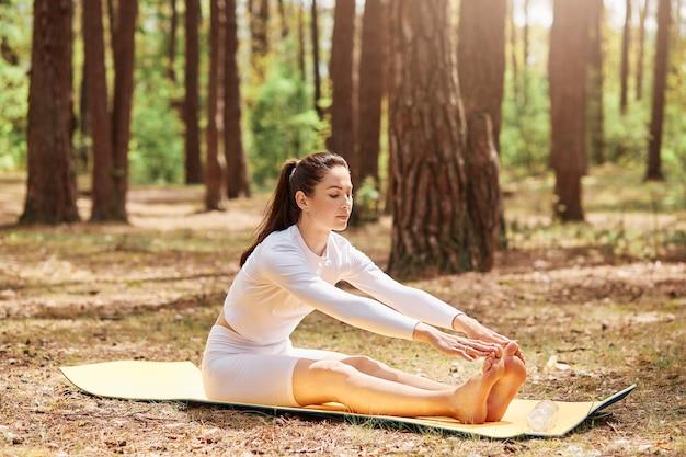 Buitenschot van jonge mooie donkerharige vrouw met witte sporttop en leggins, yoga beoefenen in open lucht, zittend op mat in sit-up pose