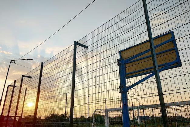 Buitenshuis minivoetbal en basketbalveld met ballenhek en basket omgeven met hoog beschermend hek.
