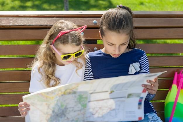 Buitenshuis portret kinderen toeristen. met kaart van de stad op de bank