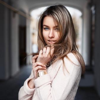 Buitenshuis portret van een jonge mooie vrouw in modieuze kleding