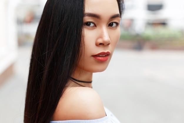 Buitenshuis portret van een mooi aziatisch meisje op de van de stad.