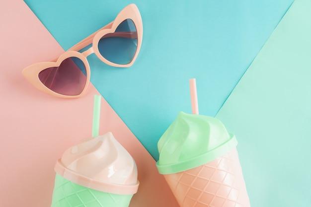 Buitensporig glas met de zonnebril van de hartvorm op pastelkleurenachtergrond, de zomerconcept