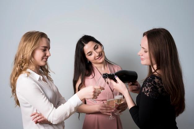 Buitensporige glimlachende vrouwen die champagne gieten