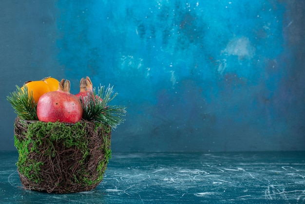 Buitensporige kom met een bundel vruchten op blauw.