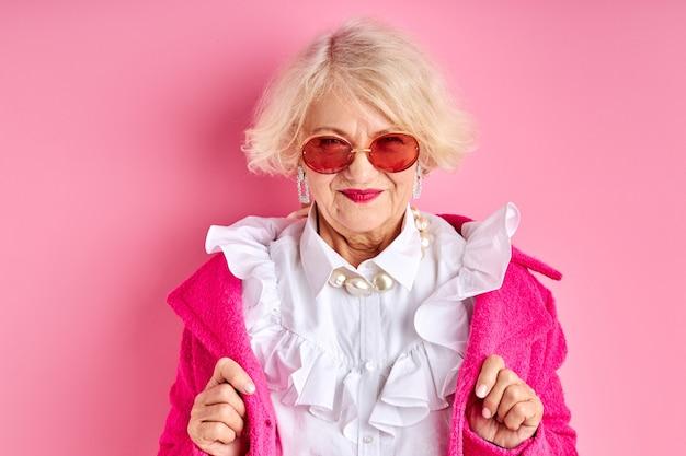 Buitensporige oude dame in oogglazen die modieuze kleding dragen, die over roze ruimte wordt geïsoleerd