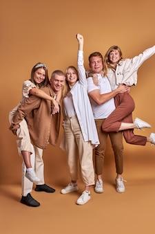 Buitensporige vriendelijke jeugd geïsoleerd in studio, portret. groep jonge mensen omhelzen elkaar, glimlachen, geluk voelen