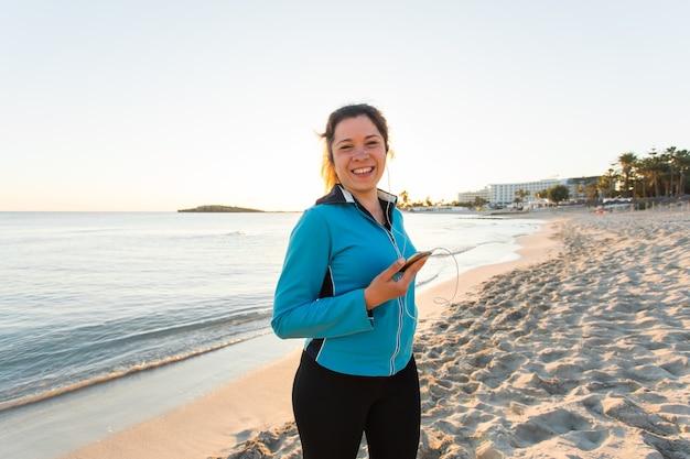 Buitensport, fitnessgadget en mensenconcept - glimlachende vrouwelijke fitness met smartphone met oortelefoons.
