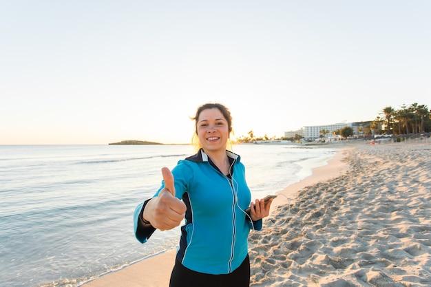Buitensport, fitnessgadget en mensenconcept - glimlachende vrouwelijke fitness toont duimen en houdt smartphone met oortelefoons vast.