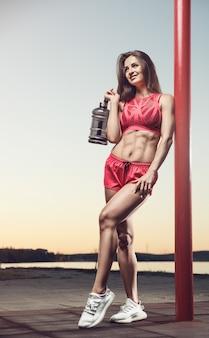 Buitensport mooie sterke sexy atletische gespierde jonge kaukasische fitness vrouw met fles water drinken bij training in de sportschool op dieet