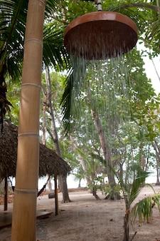 Buitenstranddouche opgehangen aan een bamboepaal in een zanderig bos