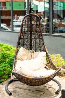Buitenterras met rieten schommelstoel