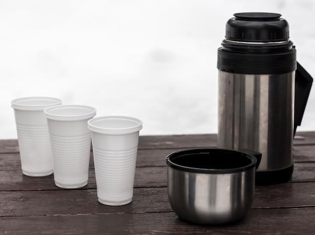 Buitenthermoskan met hete thee en wegwerpglazen in de winter op een bankje in de natuur.