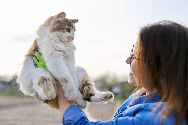 Buitenvrouw die huiskat in de armen houdt en met haar praat, vriendschap van de eigenaar en huisdier