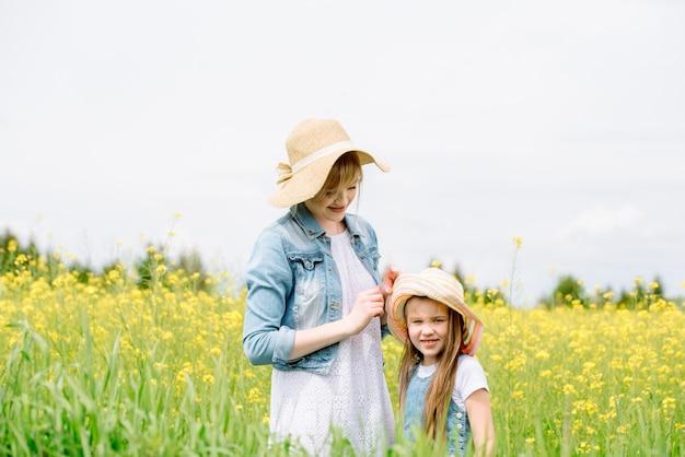 Buitenwandeling. zomer in het veld. gele bloemen, weg. moeder knuffelt haar dochter, heeft spijt en beschermt. opvoeding en zorg.