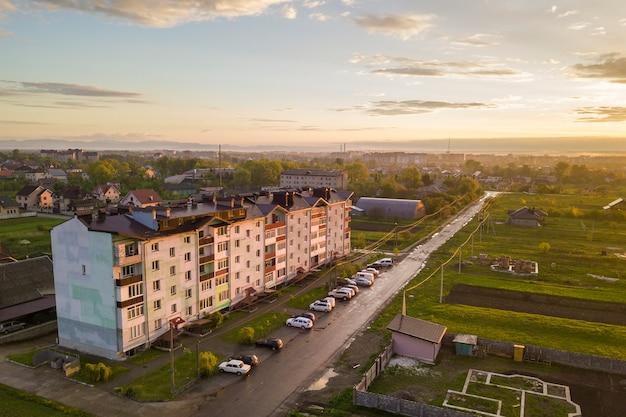 Buitenwijk landschap, appartementengebouw. geparkeerde auto's langs slechte weg op de lentedag op blauwe hemel exemplaarruimte