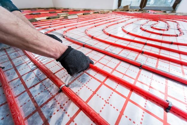 Buizenfitter installeert systeem van vloerverwarmingssysteem thuis