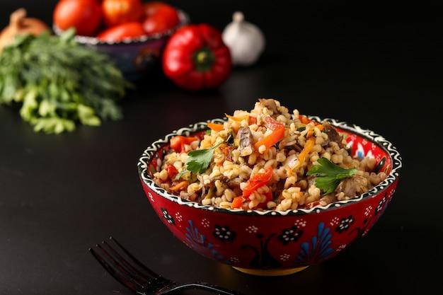 Bulgur met champignons en groenten in een kom op een donkere, vegetarische oosterse schotel,
